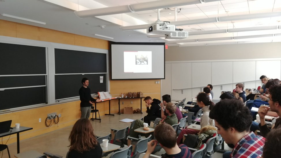 A male student presents a seminar before an audience of fellow students and postdocs.