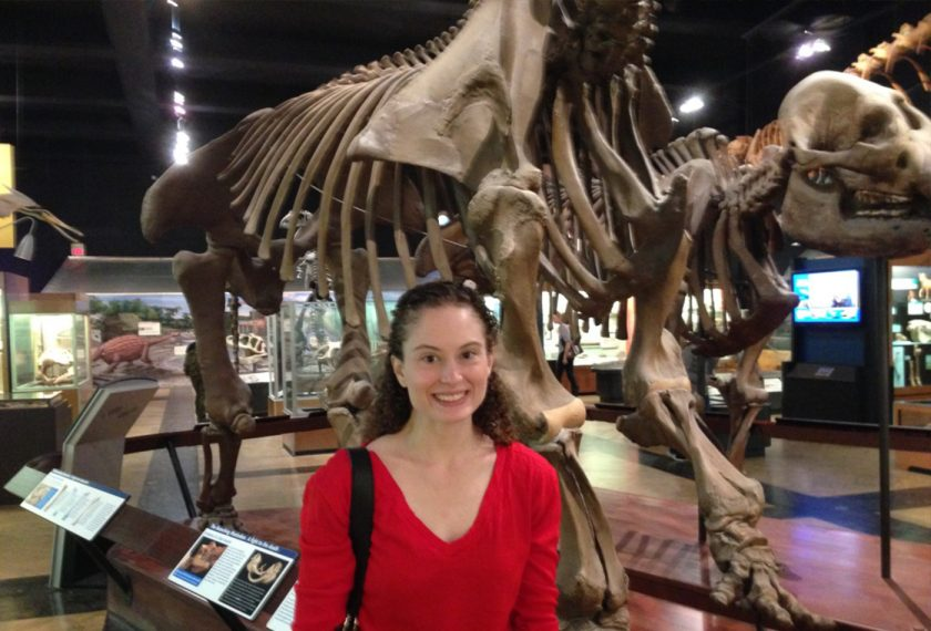 A young woman stands in front of a giant dinosaur skeleton.