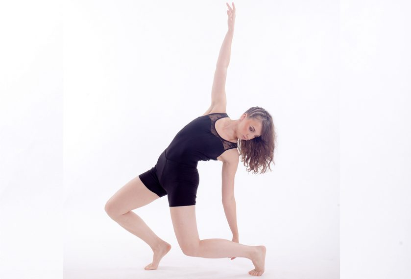 A female dancer in a black sleeveless unitard crouches in a dance pose with one hand in the air.
