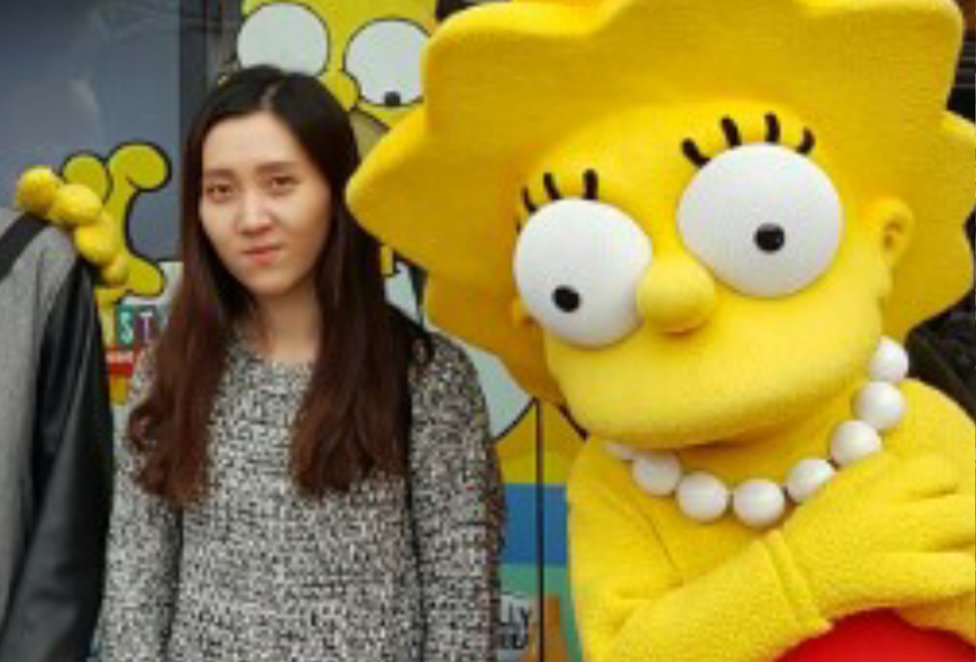 A female graduate student stands next to a bright yellow Lisa Simpson theme park character.