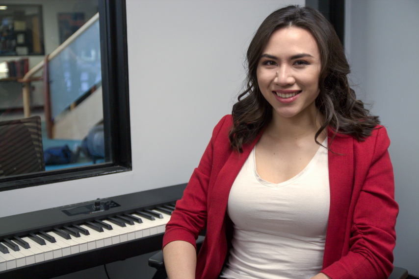 A young woman with brown hair sits smiling in front of a piano keyboard.