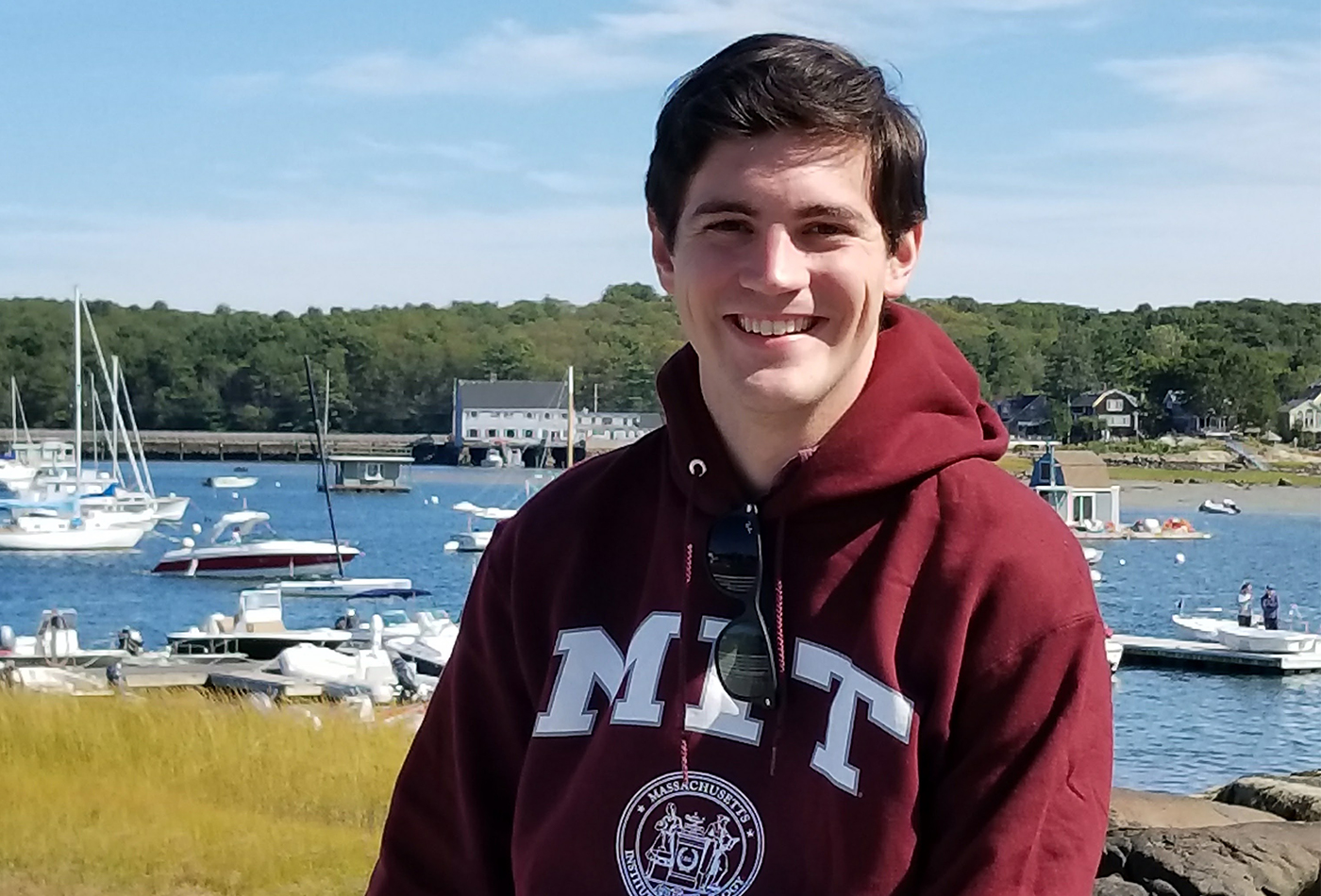 A male graduate student in an MIT sweatshirt stands in front of a coastal vista.