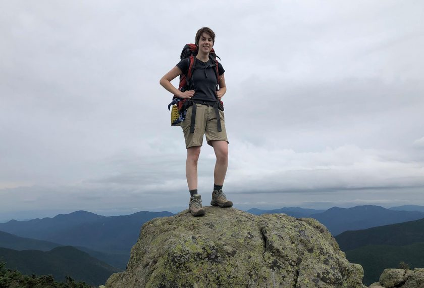 A female graduate student in hiking gear stands on top of a mountain.
