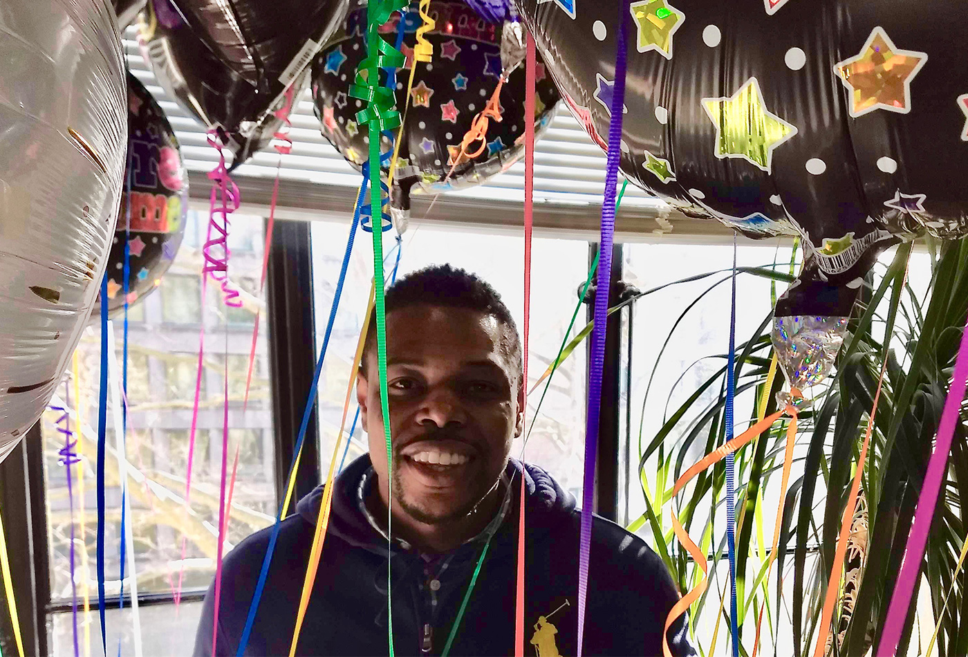 A man holds a bunch of balloons and smiles.