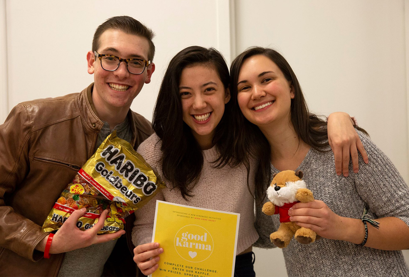 Three students smile together holding stuffed animals and gummy bears.