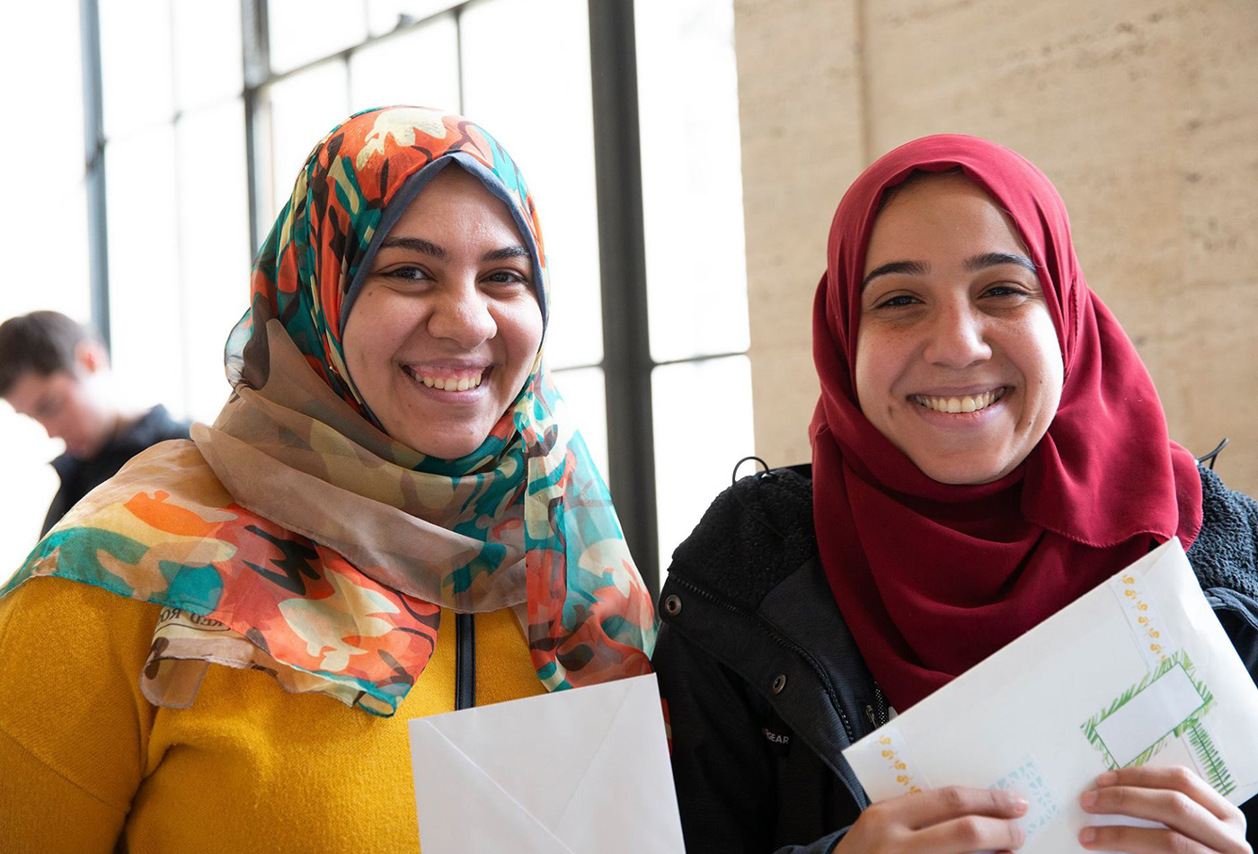 Two women smile holding the letters that they've written.