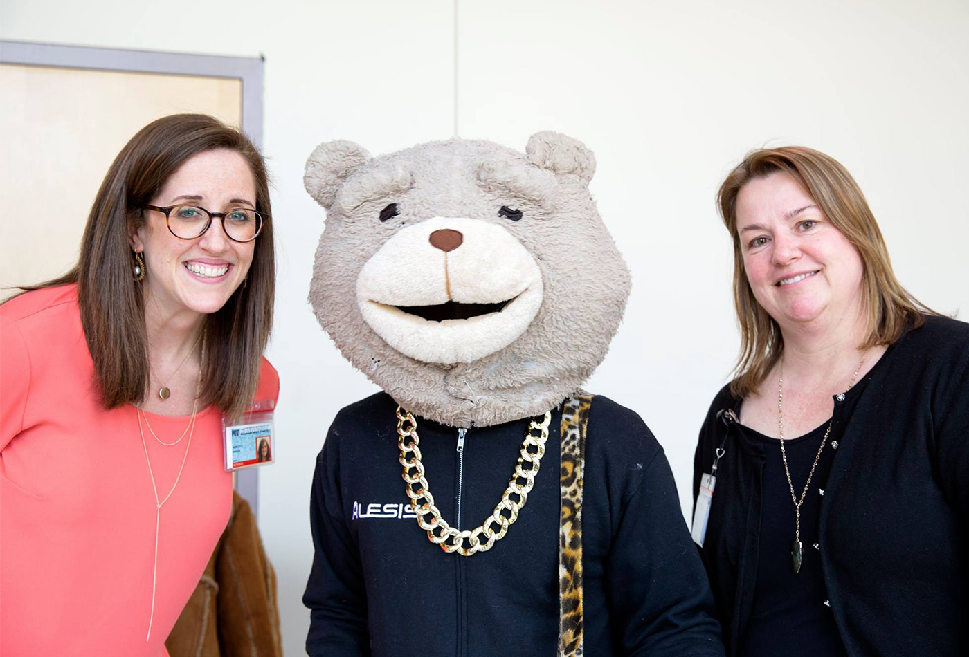 A teddy bear character poses between two women.