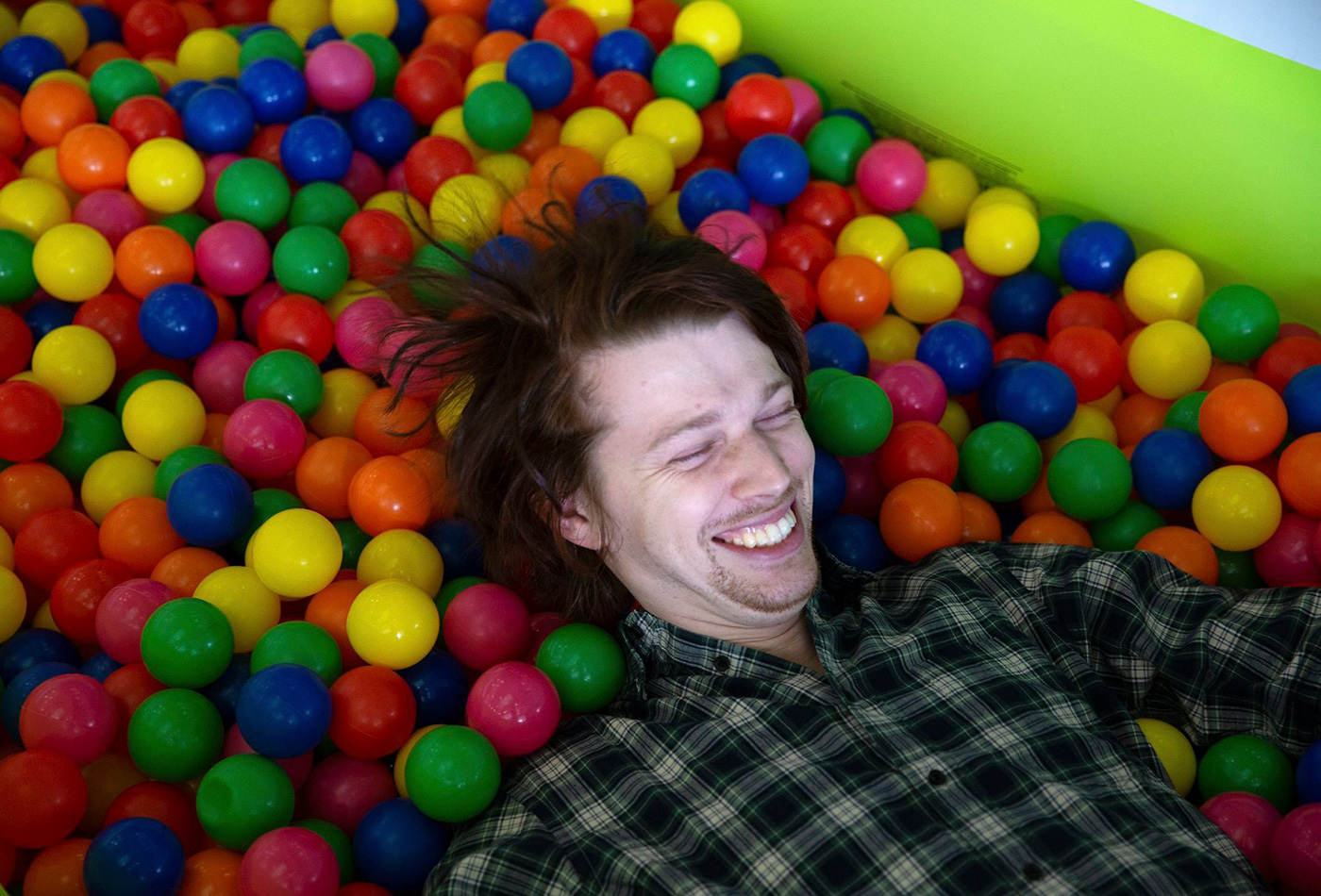 A student smiles in a ball pit.