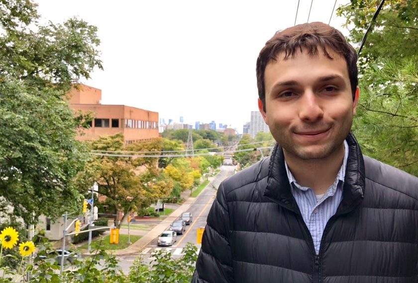 A male graduate student stands with a city vista behind him.