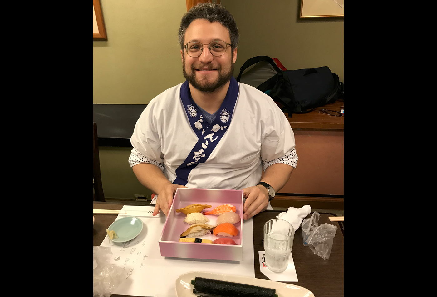 A male graduate student sits at a Japanese restaurant displaying a box of sushi.