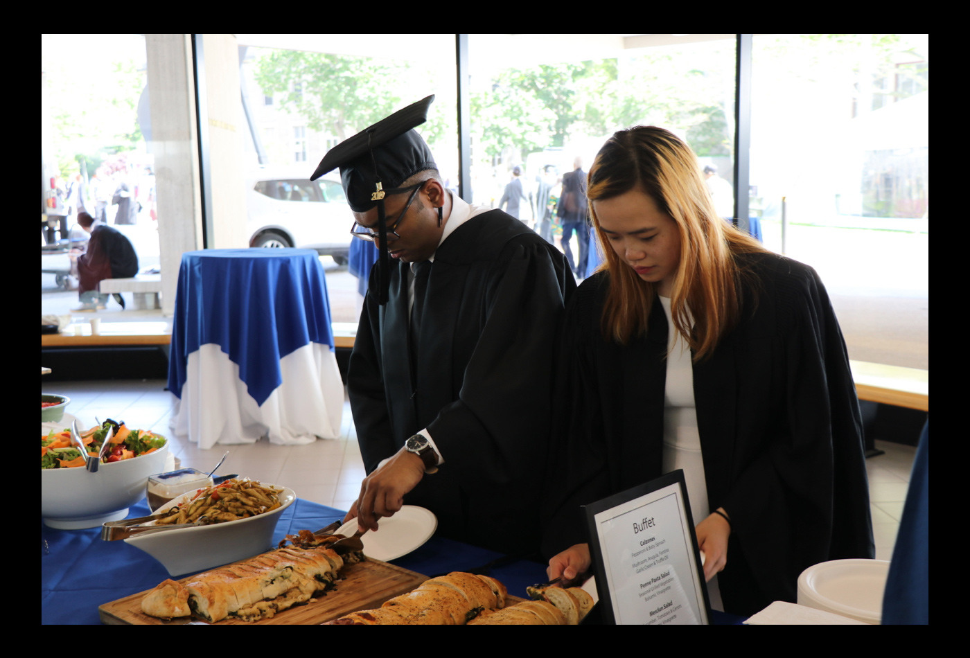 Two Chemistry graduates help themselves to a buffet.