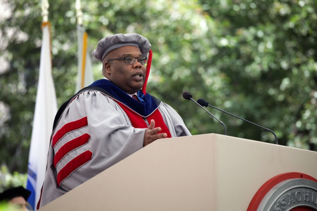 Squire Booker stands behind a podium in his doctoral regalia, addressing the crowd.