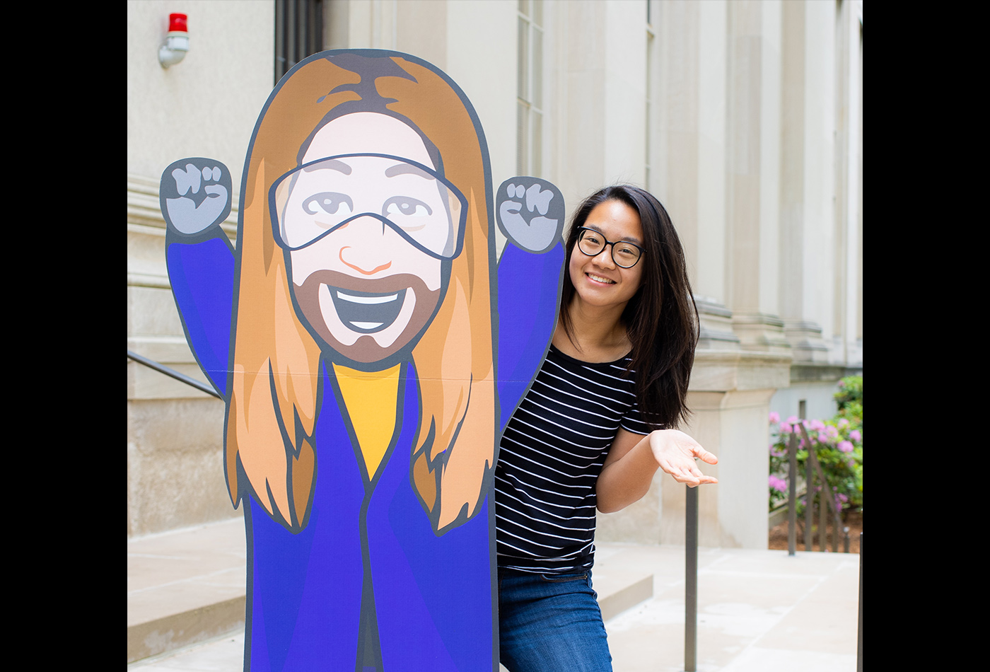 A female graduate student poses with a large cartoon cardboard cutout of a researcher.