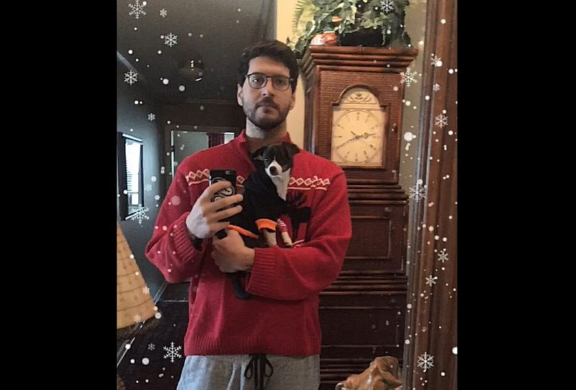 A male graduate student takes a self portrait while wearing a Christmas sweater and holding a small black and white dog, who is also wearing a sweater.