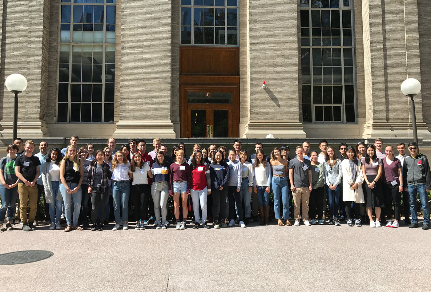 A group shot of 50 graduate students in front of an MIT building.