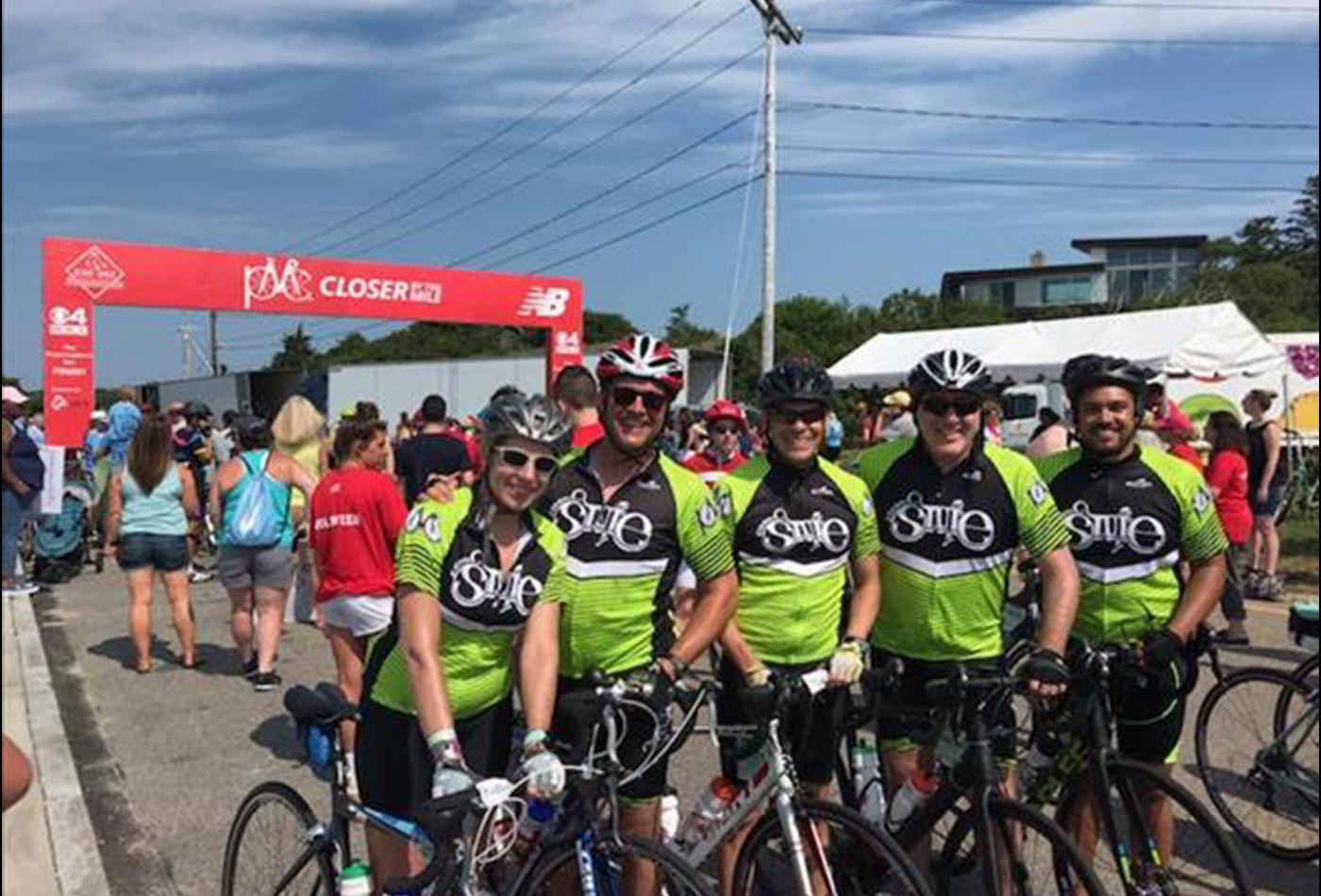 A team of bicyclists smile together on their bikes.