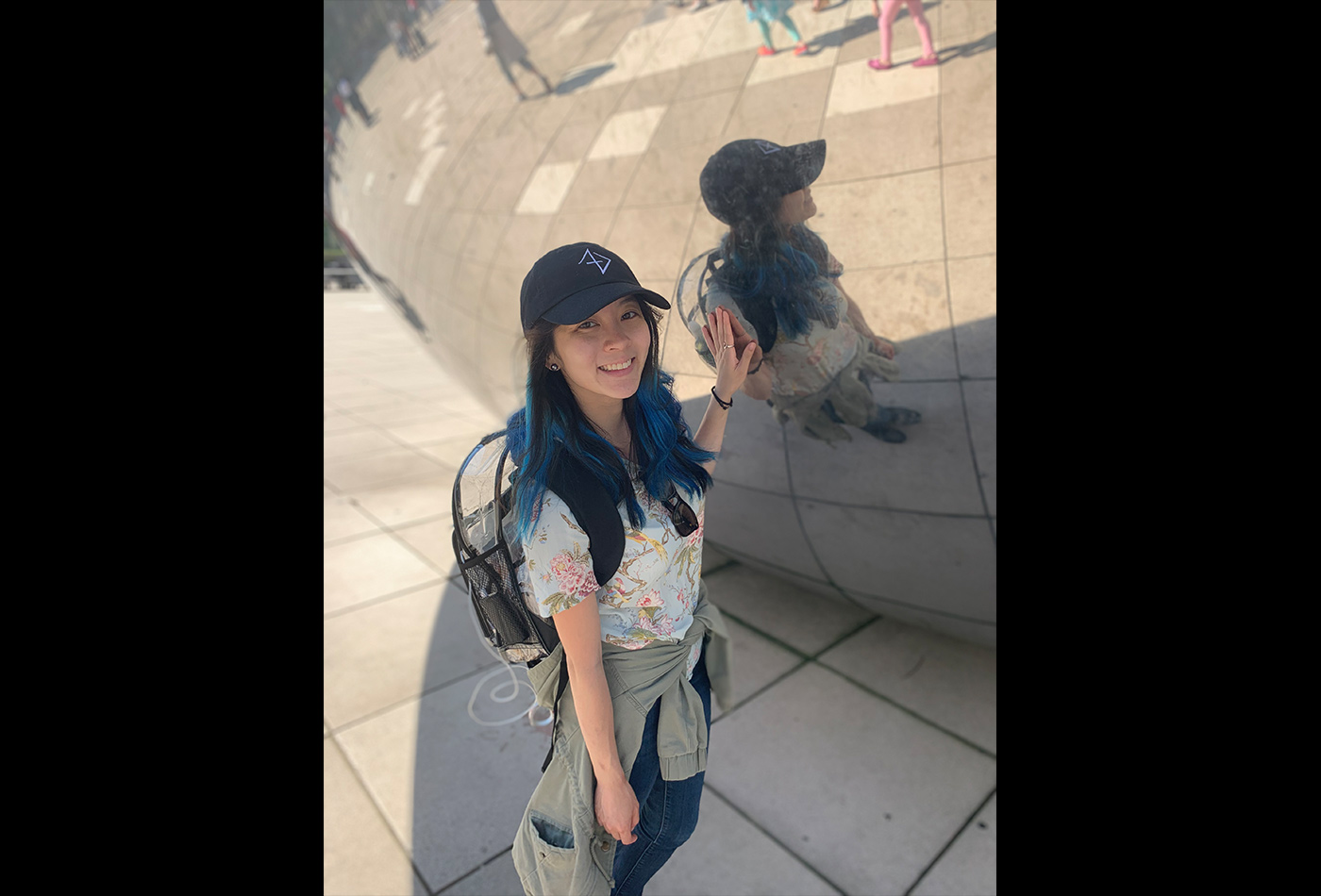 A female graduate student smiles beside the landmark Chicago silver bean.