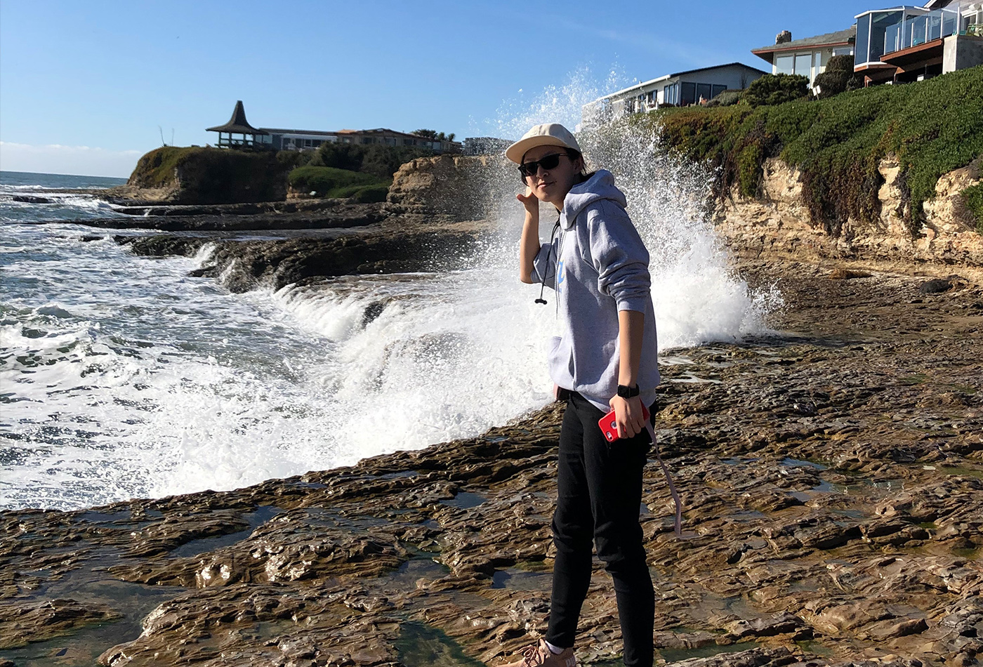 A female graduate student stands on a bluff with a wave crashing behind her.