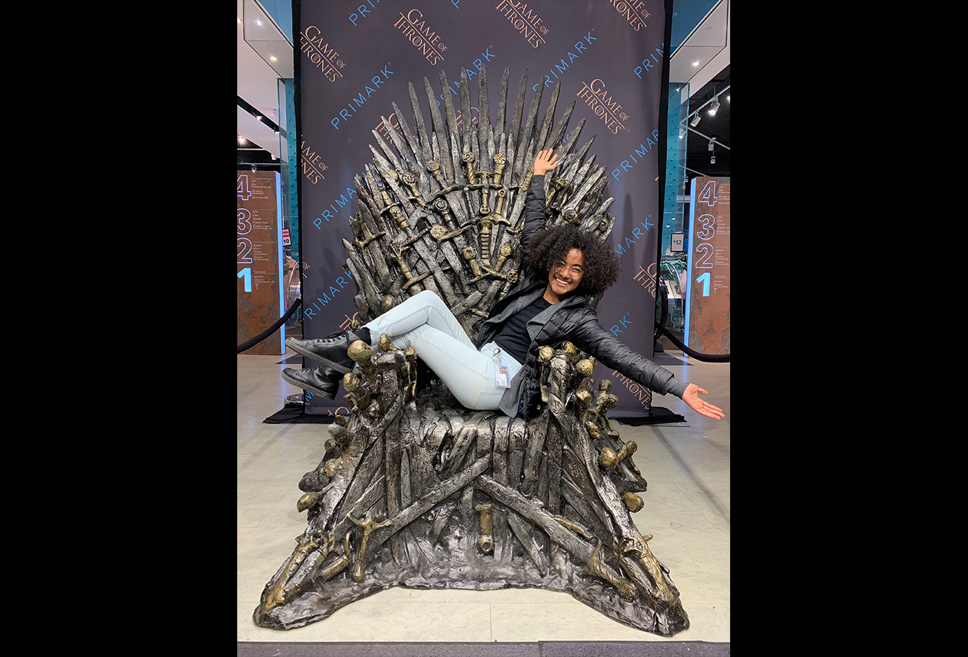 A female graduate student sits on a replica of the Iron Throne made of swords from Game of Thrones.