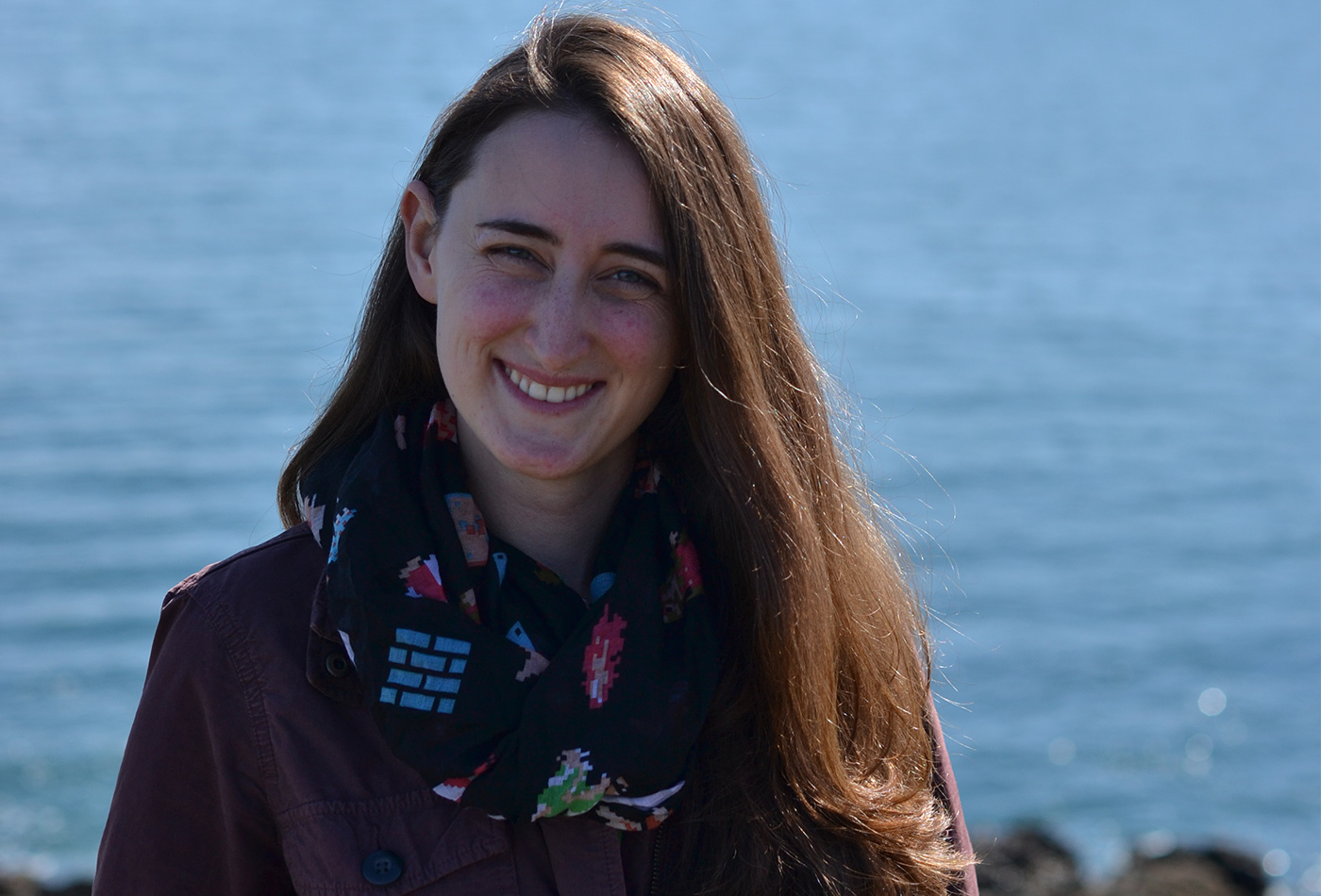 A female graduate student smiles before a body of water on a sunny day.