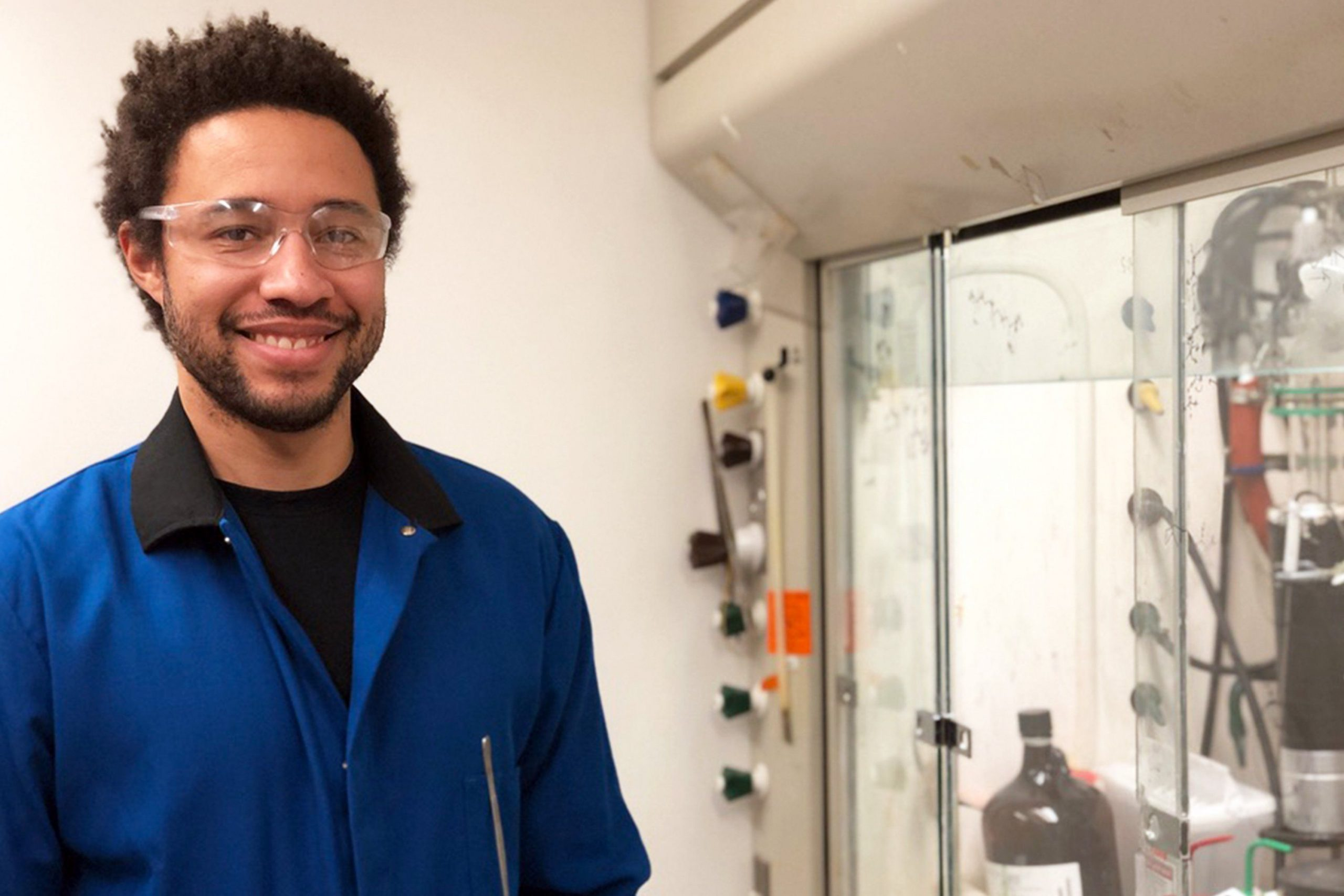 Image of postdoc Ben McDonald in front of a workstation in a lab.