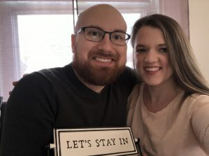 A man and a woman smile together with a sign that says Let's Stay In.