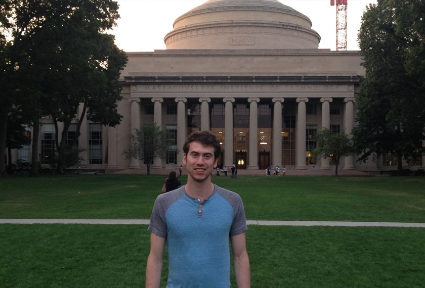 A man stands in front of the MIT dome.