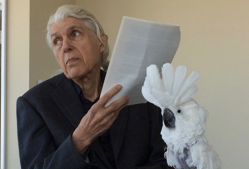 A white haired man poses beside a white cockatoo.