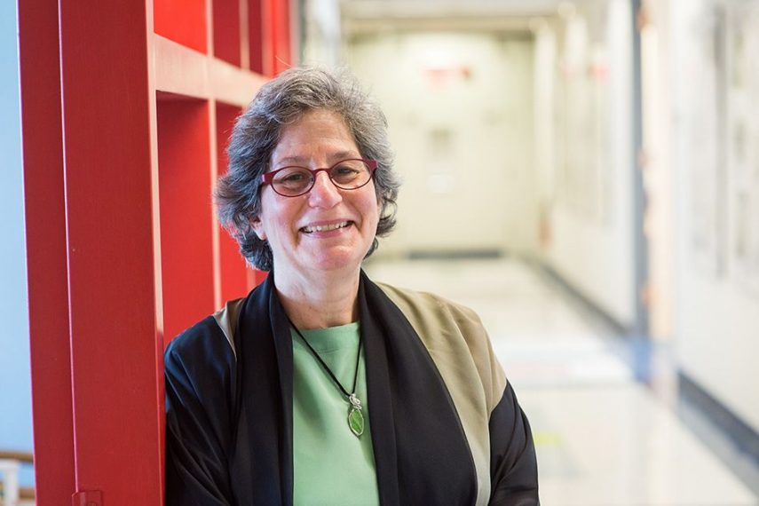 A professor is photographed in a hallway.
