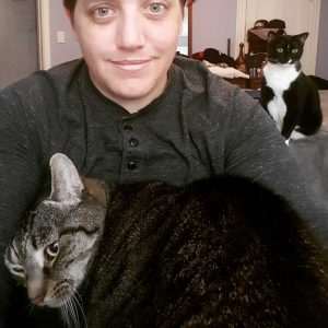 A person poses with two cats.