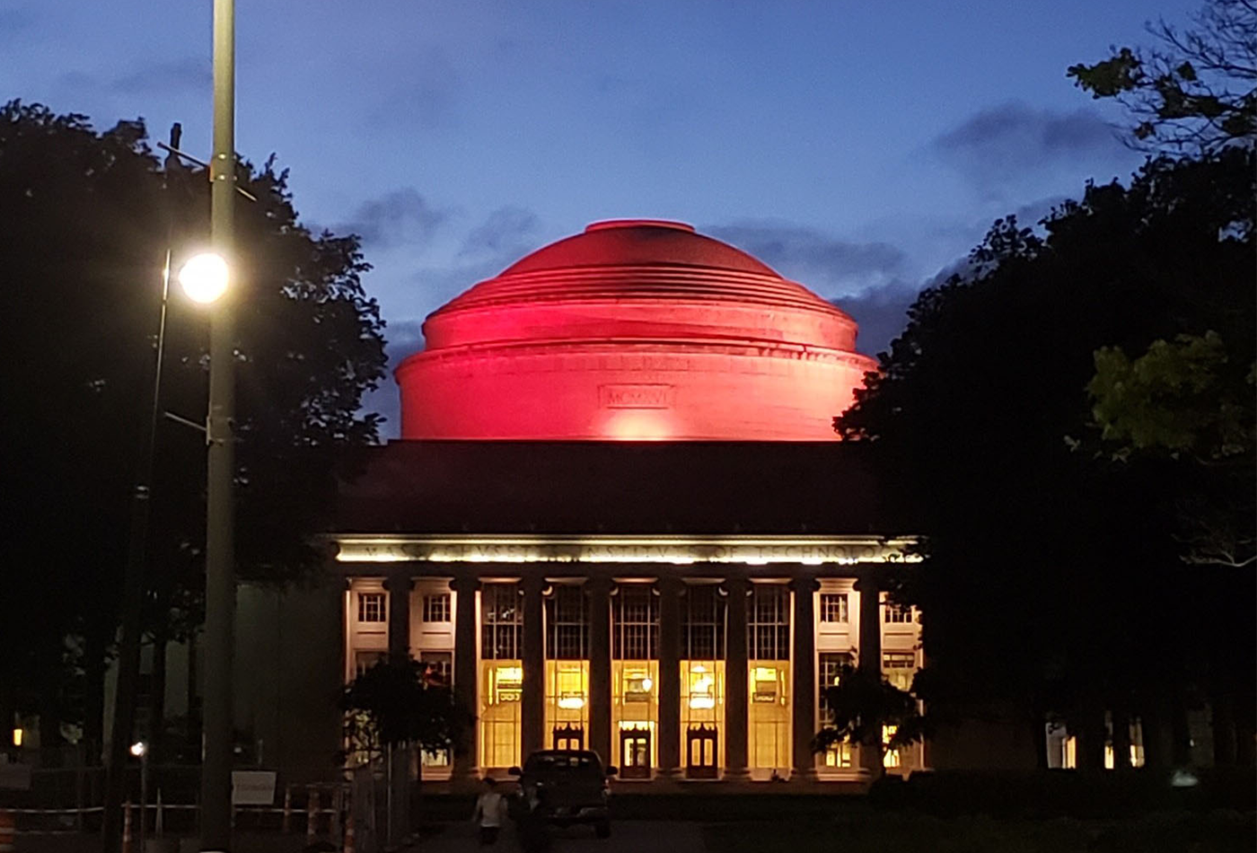 The MIT Dome lit up red at dusk.