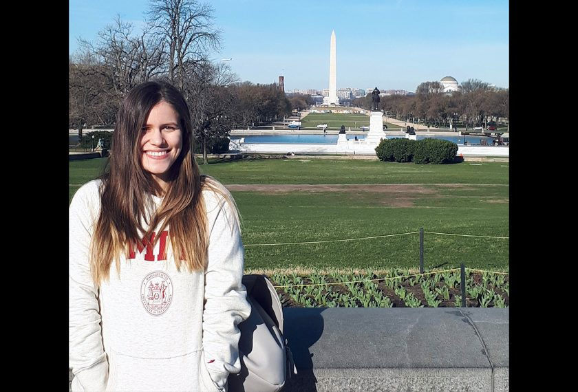 A female graduate student stands in front of the Washington Monument
