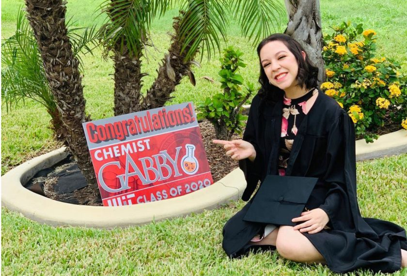 Gabriela Cazares poses in front of a sign commemorating her graduation from MIT.