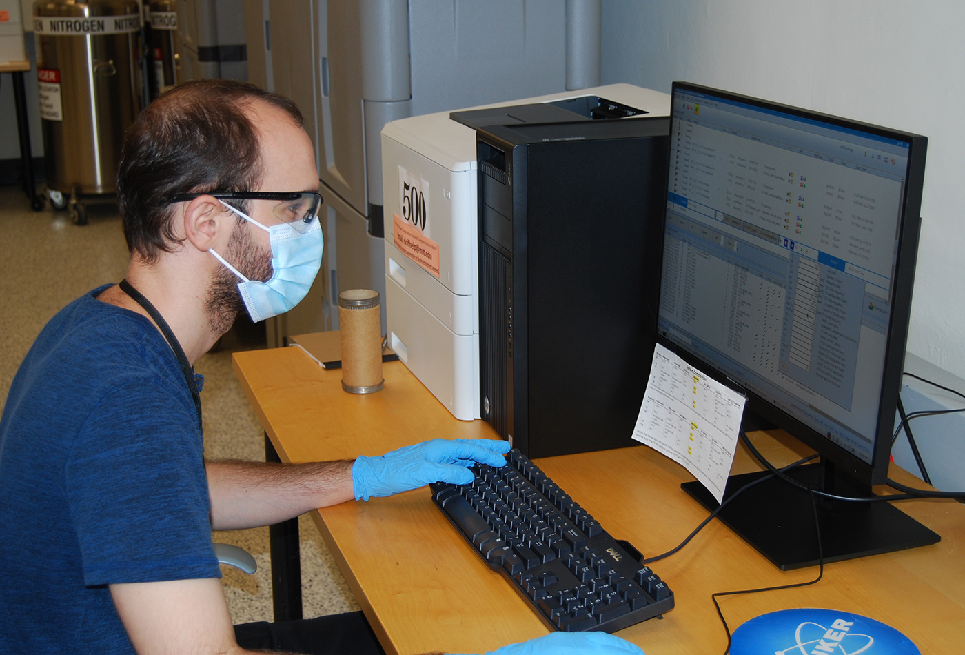 A man in gloves and a face mask works at a computer.