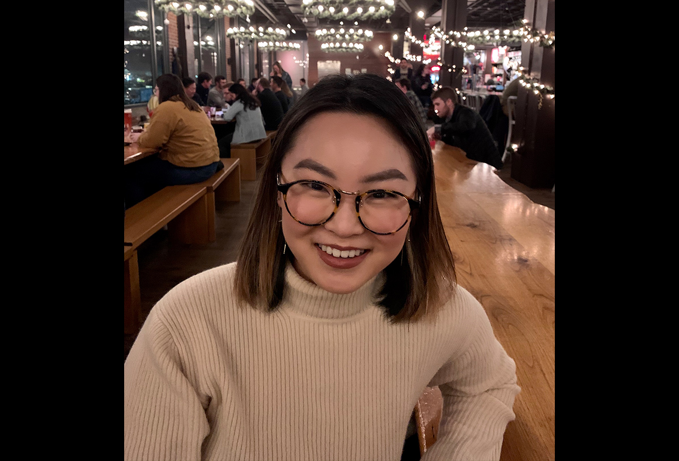 A young woman sits in a restaurant.