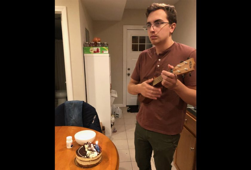 A male graduate student plays a ukelele in front of a cake with a lit candle on it.