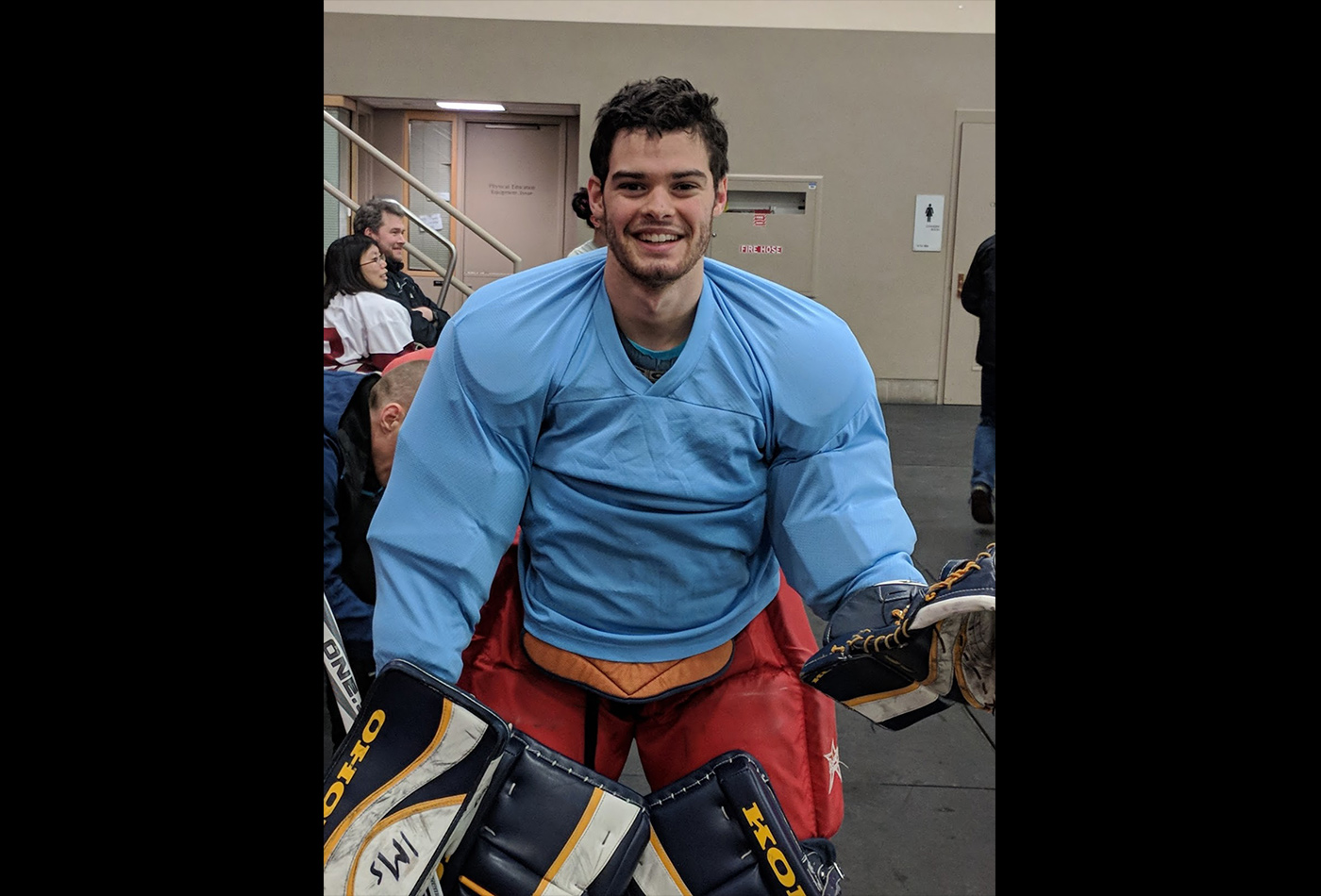 A male graduate student smiles in hockey gear.