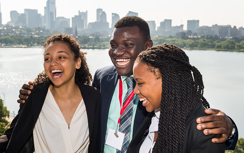 A trio of students of color smile in front of the Boston skyline.