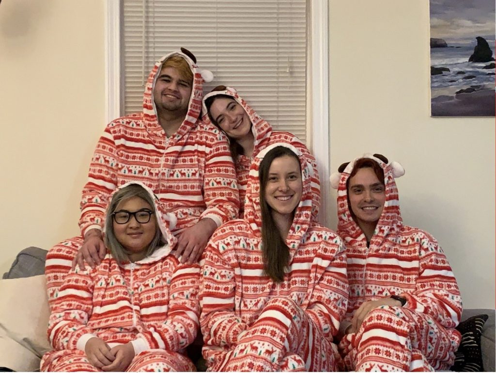 Five young adults wearing matching red and white hooded onesies.