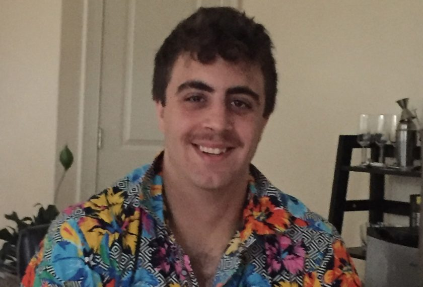 A male graduate student smiles while wearing a tropical shirt.