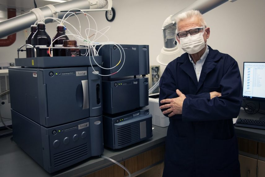 A man stands in front of a mass spectrometer.