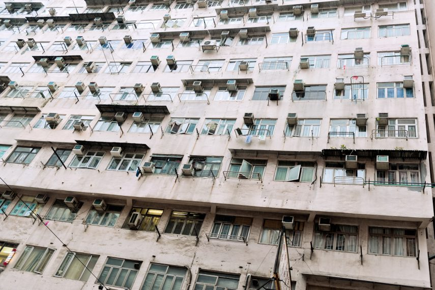 An apartment building littered with air conditioning units on every window.