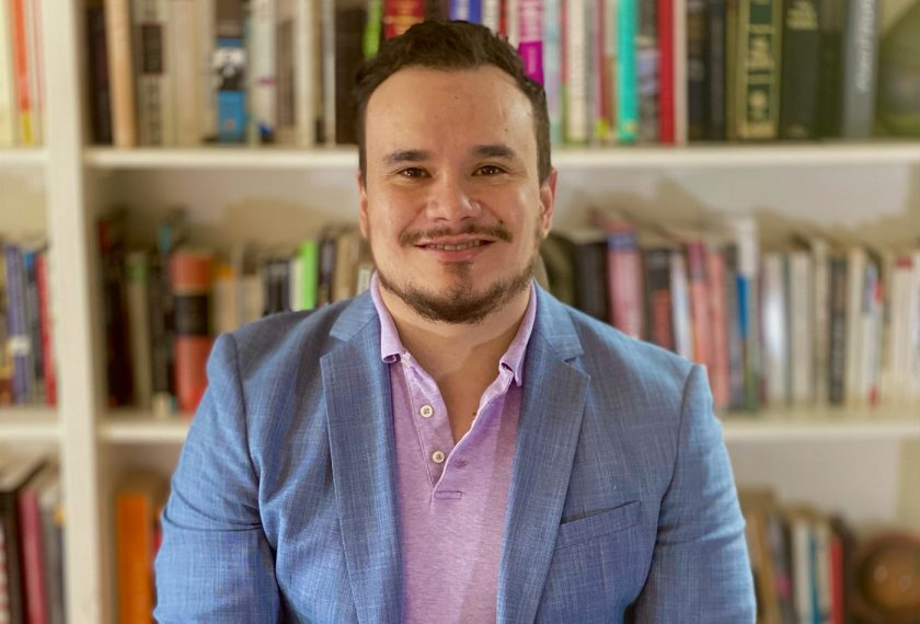 A man in a blazer smiles in front of a bookshelf.