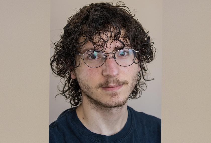 A headshot of a male graduate student wearing glasses.