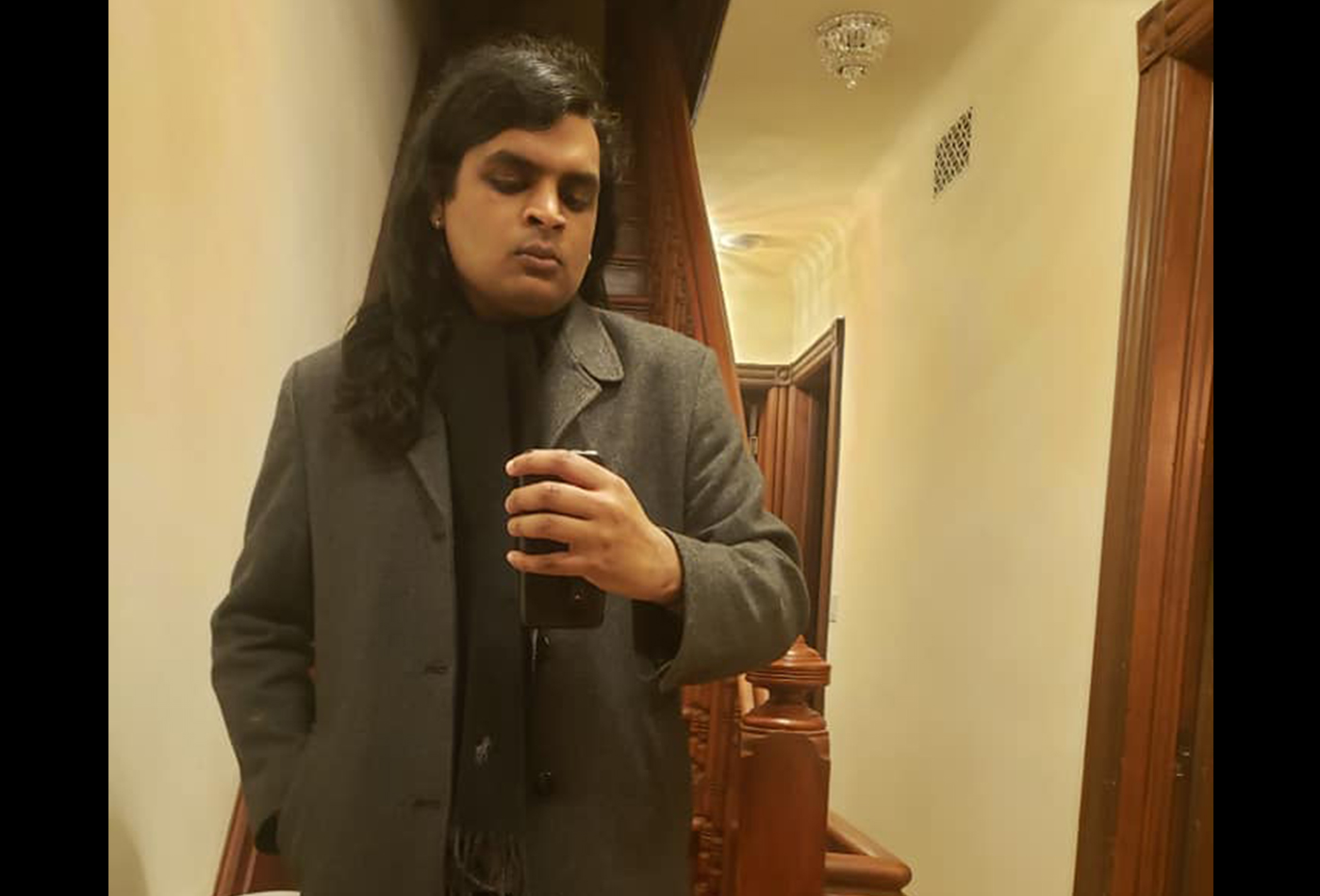 A graduate student with long black hair stands in a hallway.
