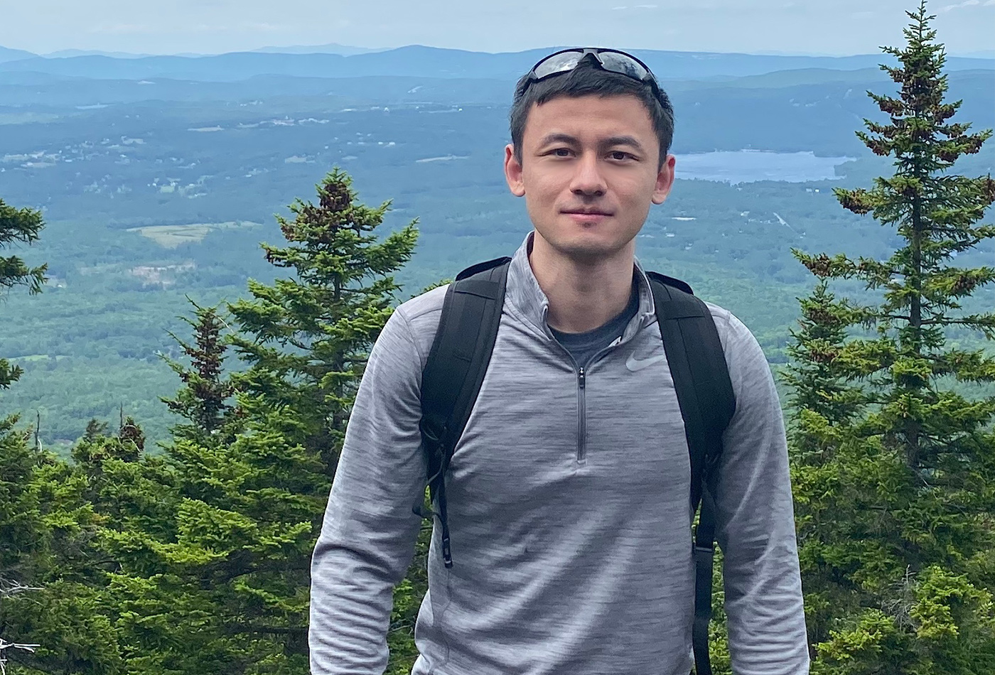 A male graduate student smiles on a mountaintop.
