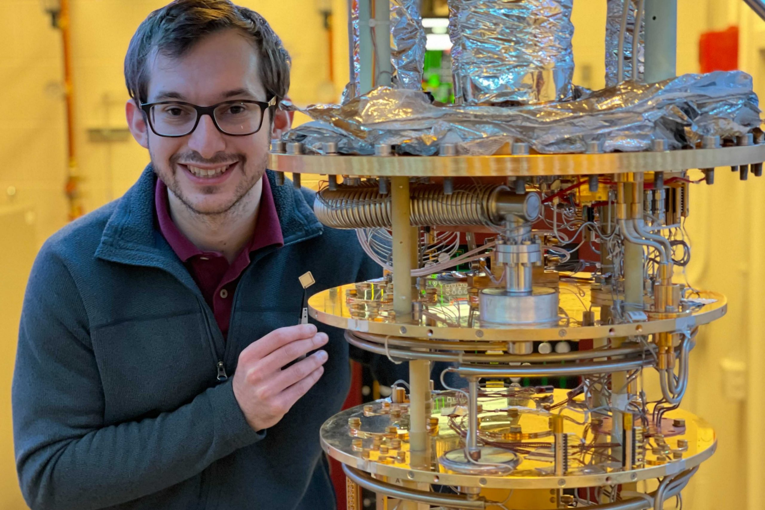 A graduate student smiles with a graphene-based electronic device.