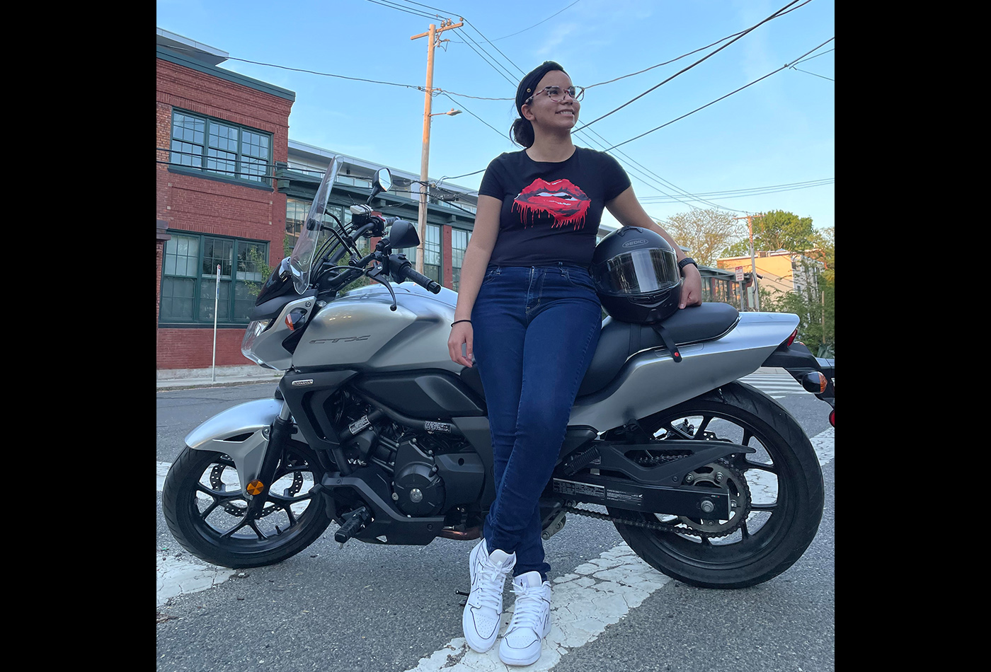 A female graduate student poses with her motorcycle.