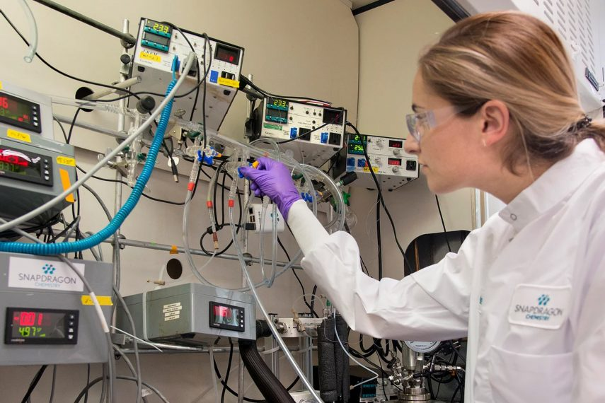 A woman works in a scientific setting.