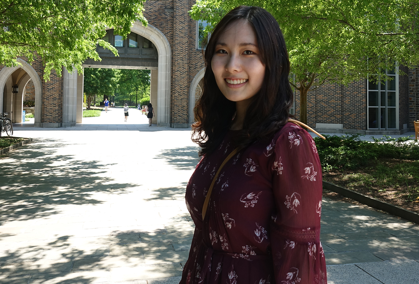 A female graduate student smiles outdoors.